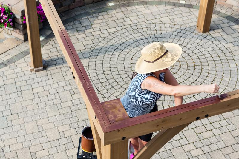 Woman staining a new wooden gazebo royalty free stock image