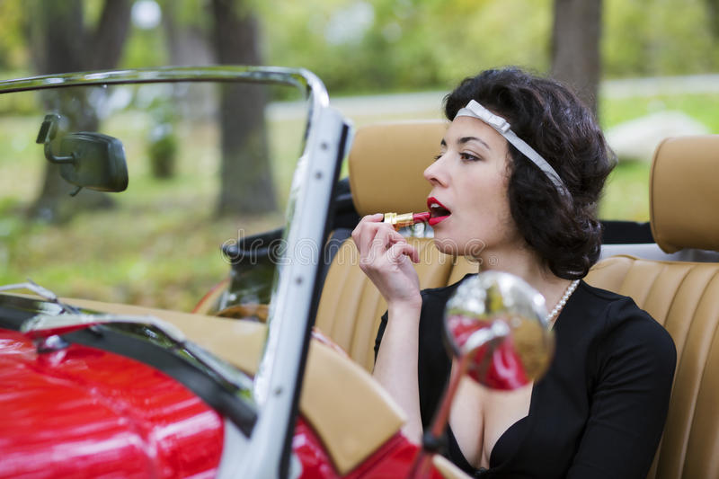 Download Woman Stains The Lips Before Car Mirror Stock Photo - Image: 34553806