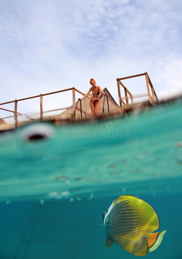 Woman on the stairs at descent to the sea and a under water view, person is visible through water drops stock photo