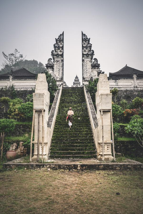 Woman on stairs to the entrance to the Pura Lempuyang temple stock photo