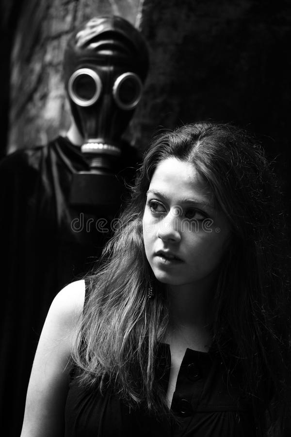 Woman and stalker. Portrait of young woman and stalker with gas mask on his face stock image
