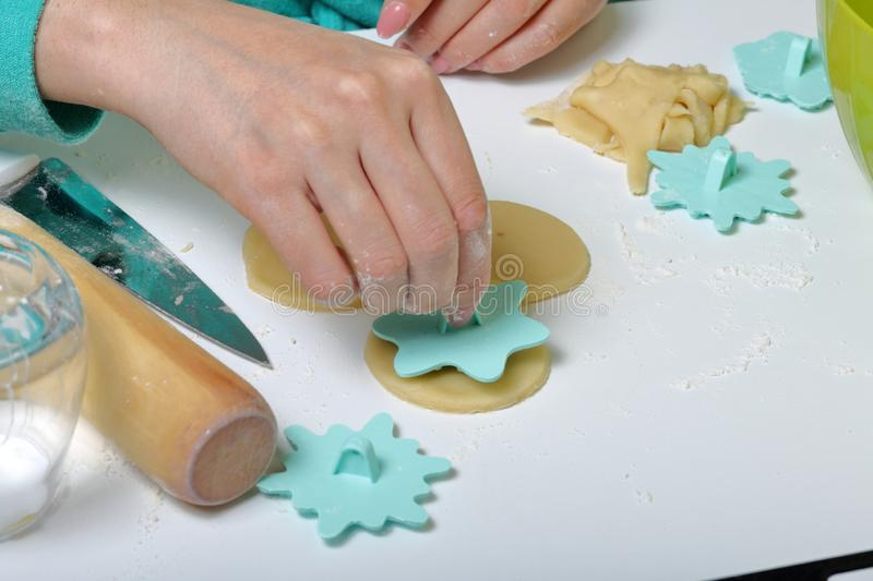 A woman with a stamp applies ornament on round blanks of rolled dough. For making marshmallow sandwiches.  royalty free stock photos