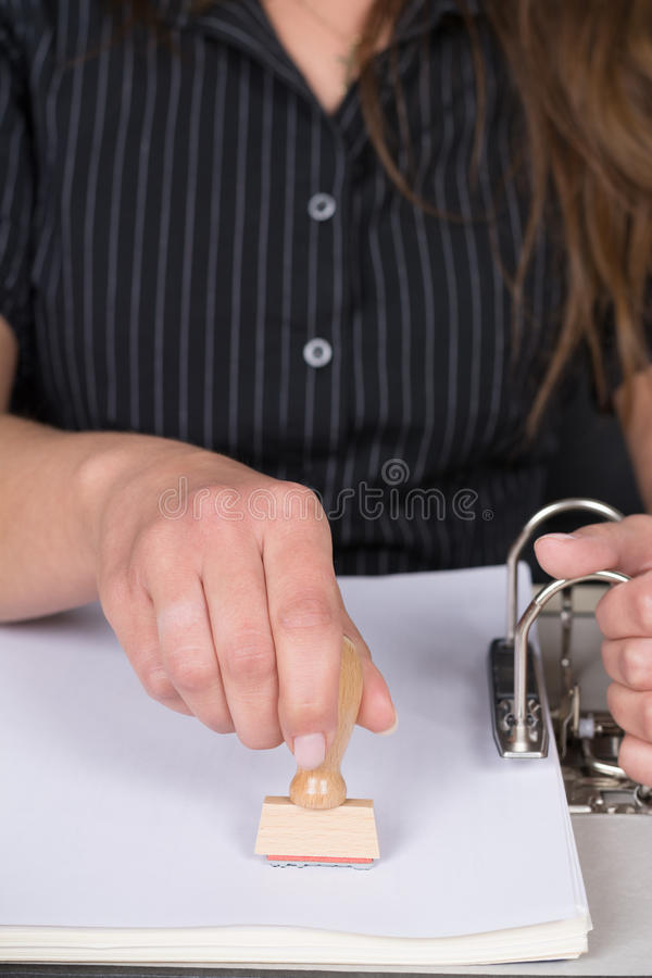 Woman is stamping a document with a stamp stock photography