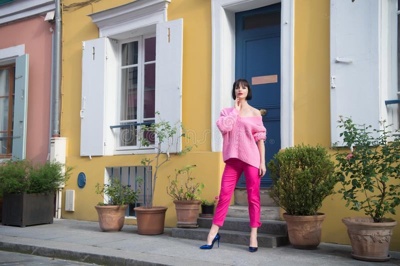 Woman stand in high heel shoes in paris, france, vacation. Woman in pink sweater, trousers on street, fashion. Beauty, look, makeu royalty free stock photo