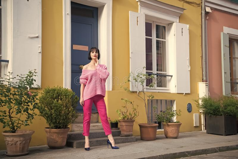 Woman stand in high heel shoes in paris, france, vacation. Woman in pink sweater, trousers on street, fashion. Beauty. Look, makeup. Fashion, style, vogue royalty free stock photo
