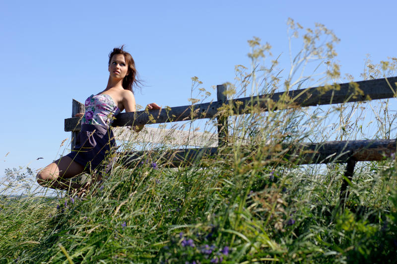 Woman stand near wooden fence