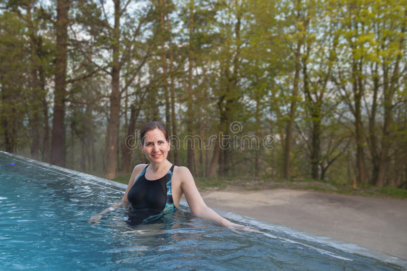 The woman stand in outdoor pool. In spring day stock photos