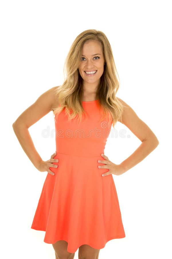Woman stand in red dress hands on hips smile stock image