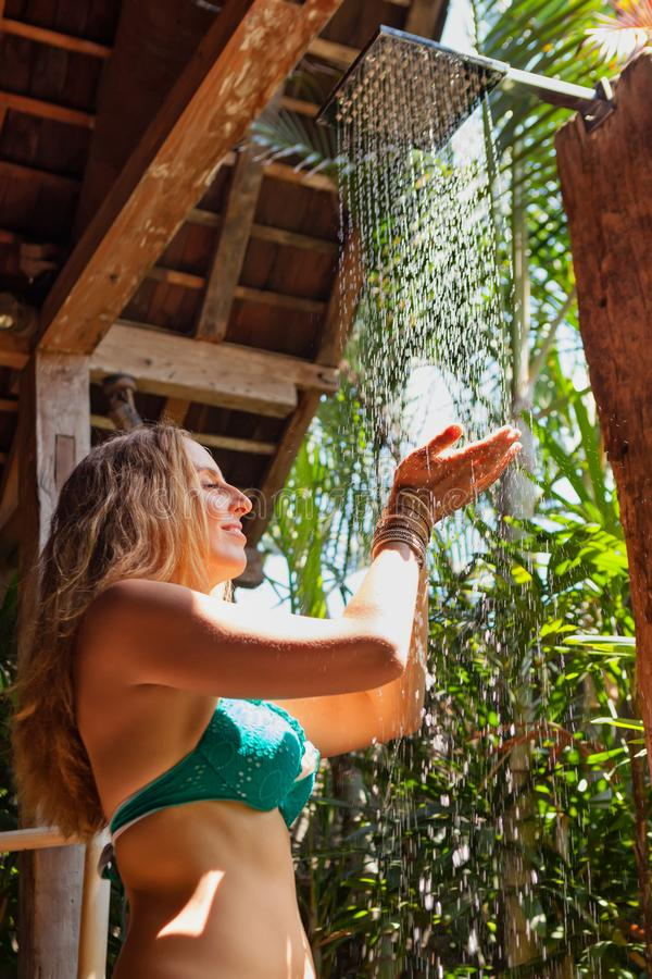 Woman stand under shower in outside bathroom with garden view royalty free stock photo