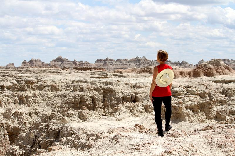 Woman wearing red standing in the Badlands of South Dakota. stock photo