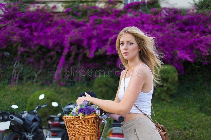 Woman standing against beautiful flowers and greenery fence with copy space. Portrait of charming stylish caucasian female enjoy a rest after an active riding stock photo