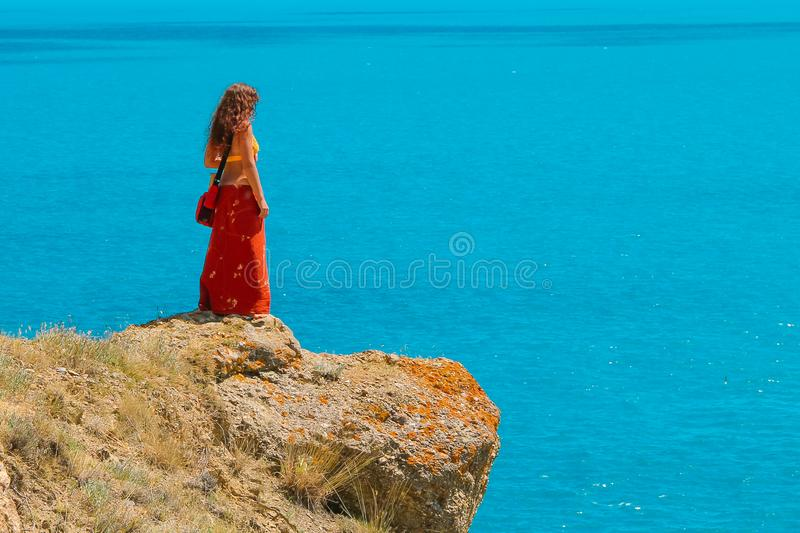 A woman is standing alone and on the edge of a cliff and looking over the blue Sea stock photo