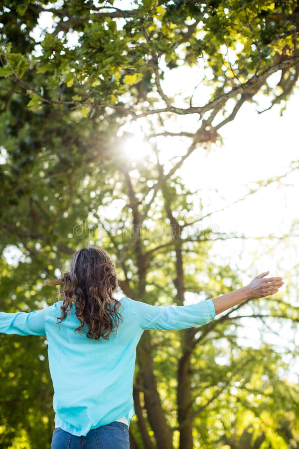 Woman standing with arms outstretched in park stock photography