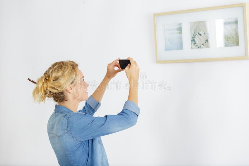 Woman standing in art museum near paintings royalty free stock photo