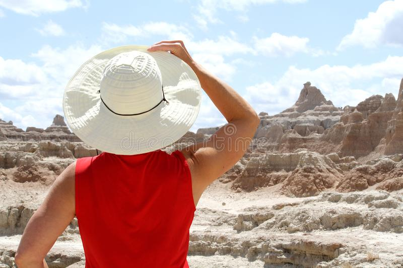 Woman holding hat looking at the Badlands of South Dakota. royalty free stock images