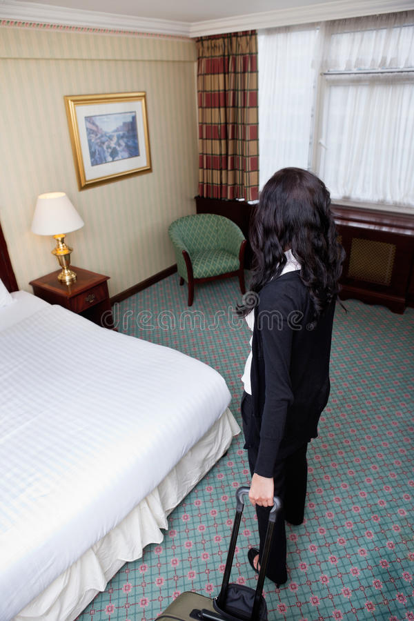 Woman Standing with Baggage in Hotel Room royalty free stock photo