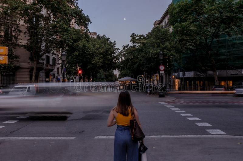Woman standing on Barcelona street. Female with bag wearing yellow t-shirt and blue jeans standing on Spanish street with vehicles in long exposure and verdant stock photos