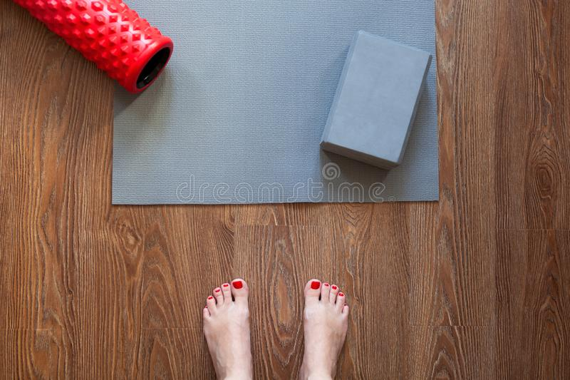 Woman is standing barefoot on floor in front of gymnastic mat and roller, she is going to do morning exercise complex. Only feet stock images