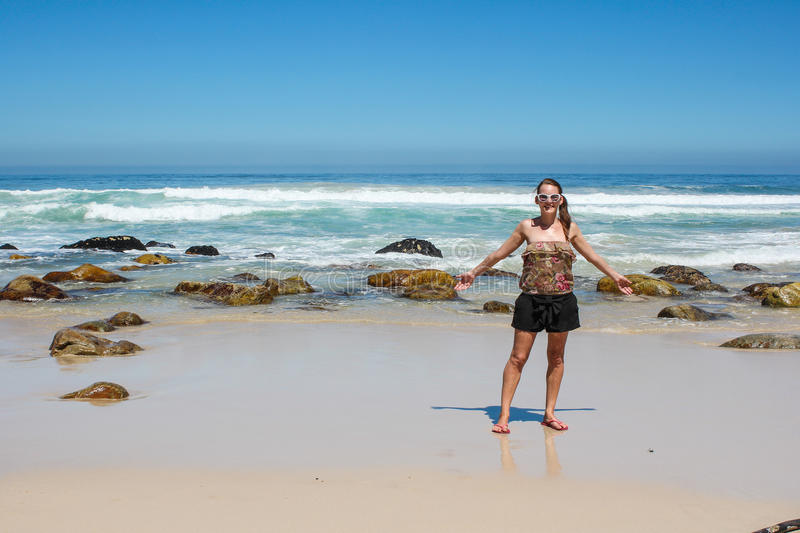 Woman standing at a beach stock photography