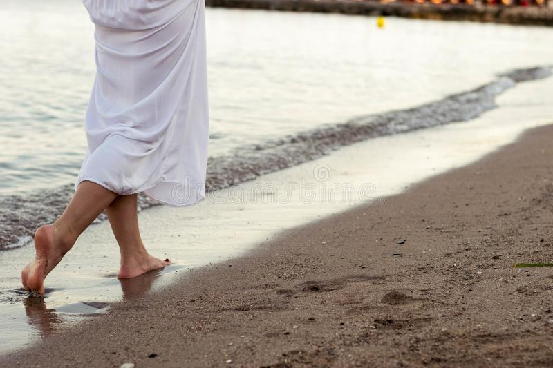 Woman standing on the beach. In white dress royalty free stock photos