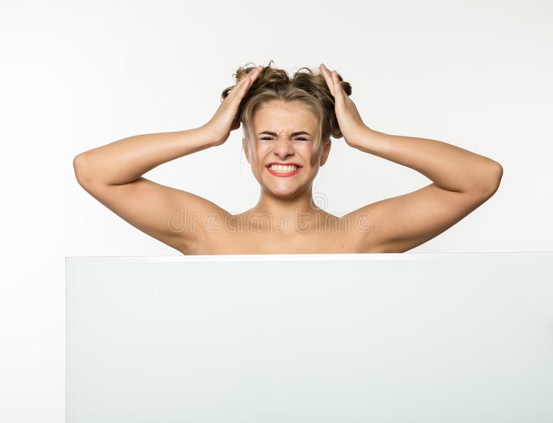Expressive girl standing behind and leaning on a white blank billboard or placard, copy space for your text stock image