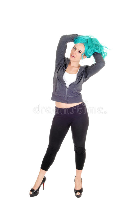 Woman standing with blue hair. A young tall woman in black tights and high heels standing isolated for white background with long blue hair stock photography