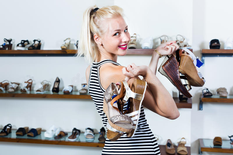 Woman standing in boutique and having many shoes. Positive happy beautiful woman standing in boutique and having many shoes in hands royalty free stock photos