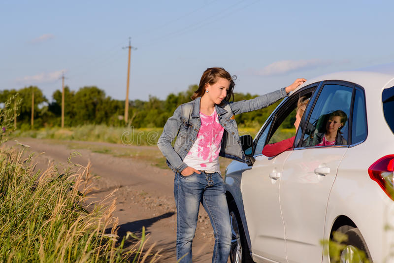 Woman standing chatting to her friend in a car. Woman standing chatting her friend car side of rural road leaning against drivers door talking through open stock photo