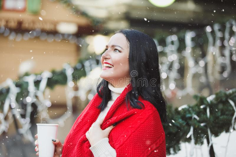 Woman standing on Christmas decorated porch of house  and drinking hot chocolate stock images