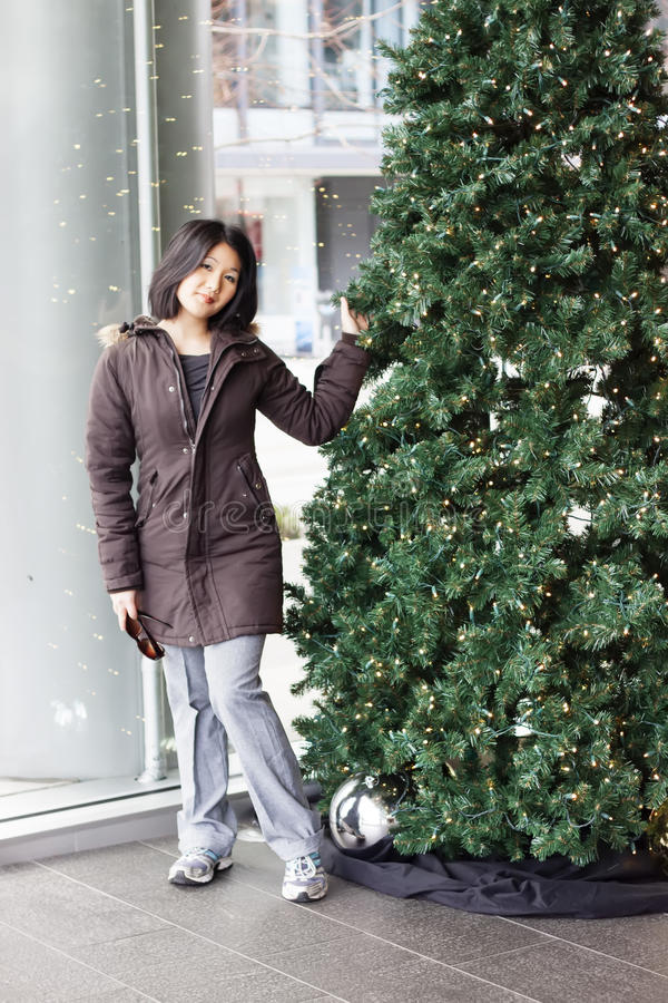 Download Woman Standing By Christmas Tree At Convention Center Stock Photo - Image: 28097994