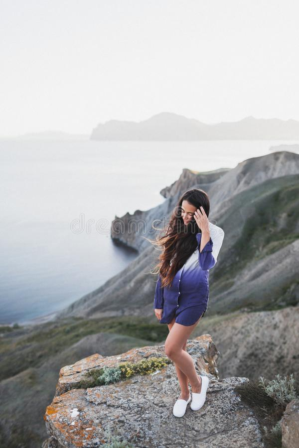 Woman on cliff with stunning view of sea coast with hills and mountains. Woman standing on a cliff with a stunning view of sea coast with background of the hills royalty free stock photography