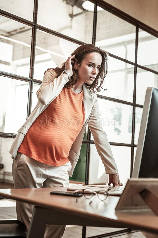 Concentrated pregnant office worker observing information on the screen. Woman standing. Concentrated pregnant office worker observing information on the screen stock images