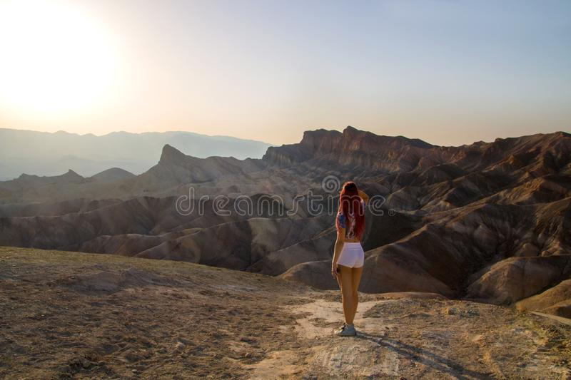 Hot sun is shining down before sunset to desert surreal landscape with beautiful travel girl standing from back, Death Valley USA royalty free stock photo