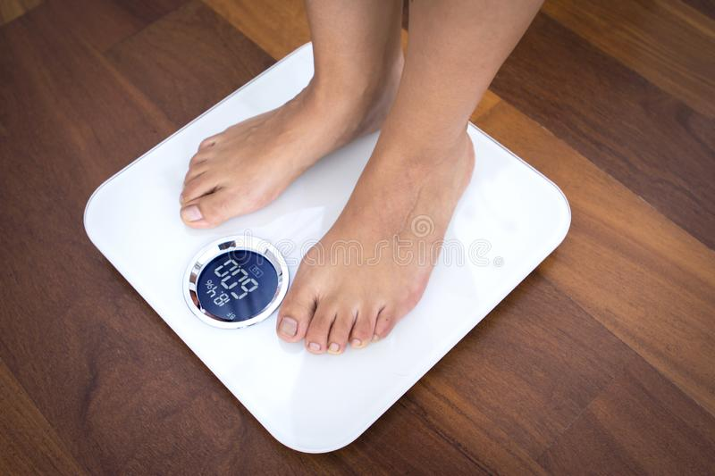 Woman standing on a digital scale with body fat analyzer stock image