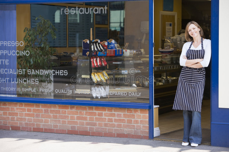 Woman standing in doorway of restaurant smiling royalty free stock image