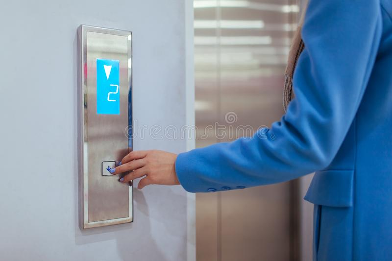 Woman Standing In Elevator And Pressing Button in shopping center.  stock photos