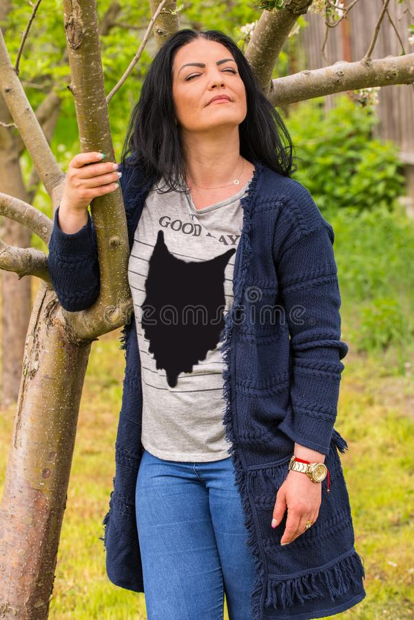 Woman standing with eyes closed near tree. Woman standing with eyes closed near spring tree and feel the nature royalty free stock image