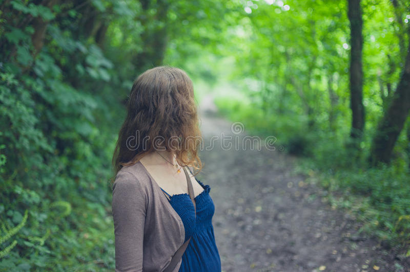 Woman standing in forest. A young woman is standing in a forest royalty free stock photography