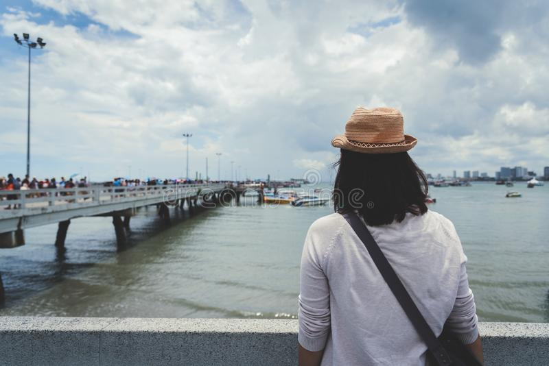 Woman standing front of the bridge. Tourist Woman standing front of the bridge with sea background. Back view of Eyeglasses girl wear hat is smiling royalty free stock photo