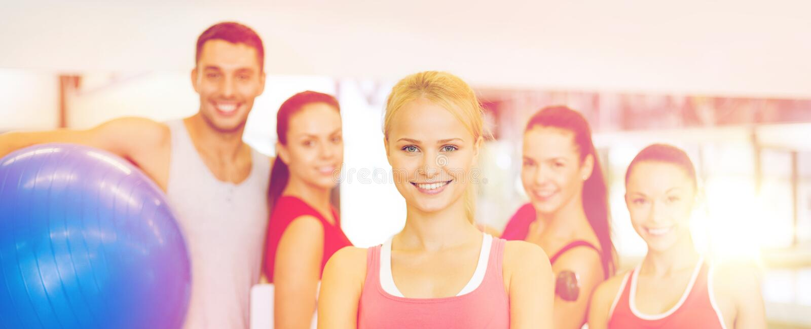 Woman standing in front of the group in gym. Fitness, sport, training, gym and lifestyle concept - smiling women standing in front of the group of people in gym stock photos
