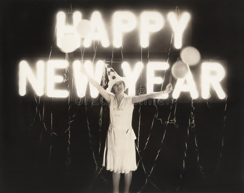 Woman standing in front of neon Happy New Year sign stock images