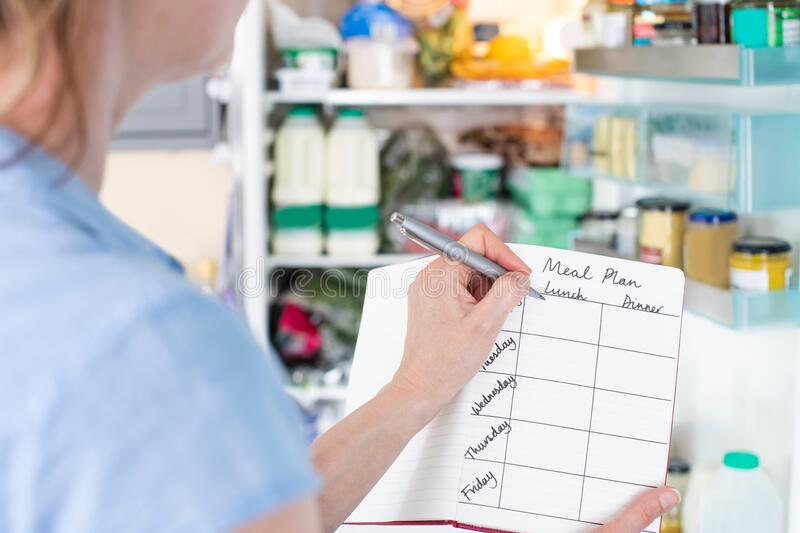 Woman Standing In Front Of Refrigerator In Kitchen With Notebook Writing Weekly Meal Plan. Woman Stands In Front Of Refrigerator In Kitchen With Notebook Writing stock photo
