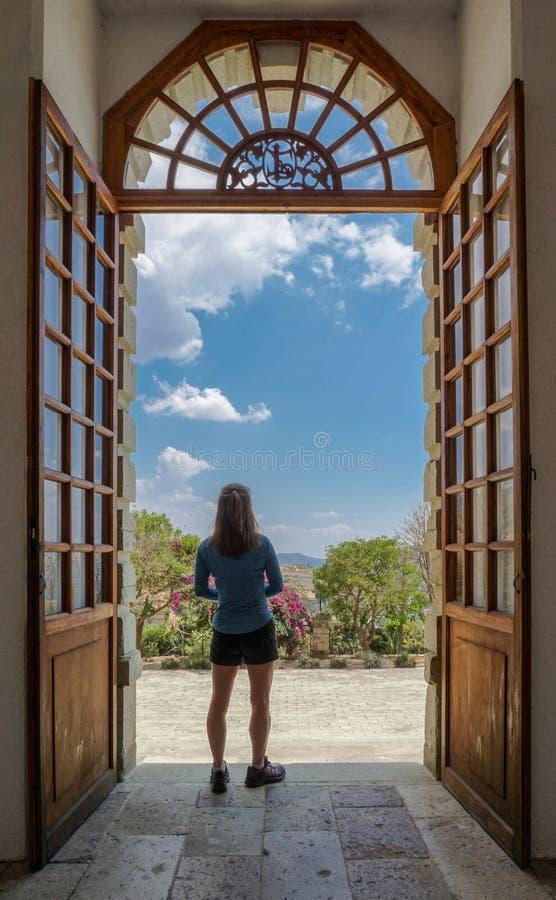 Woman standing gazing out doorway stock photos