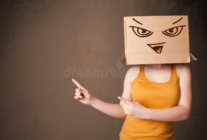 Woman standing and gesturing with a cardboard box on her head with evil face royalty free stock images