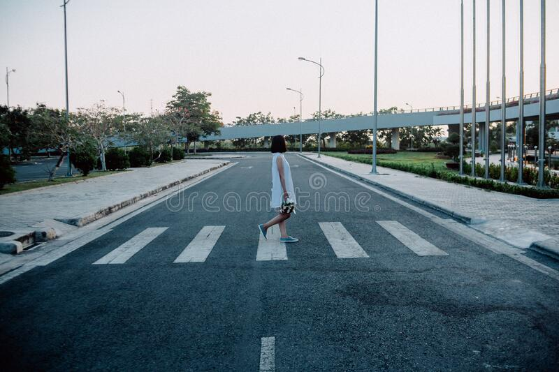 Woman Standing on Gray and White Road Crosswalk stock images