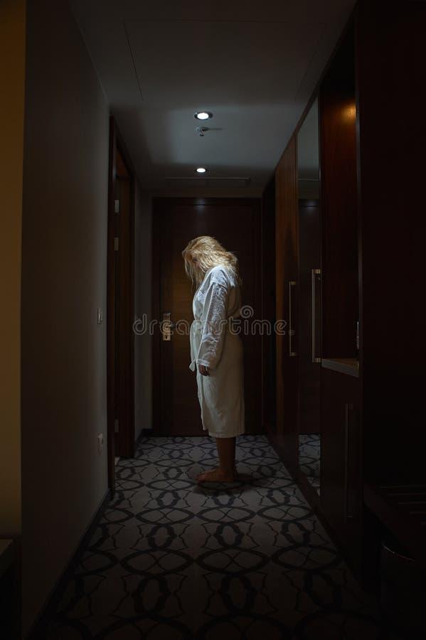 Woman standing, head bowed, in the Hallway. Sleepwalker Woman with white Bathrobe standing, head bowed, in the Hallway royalty free stock photography