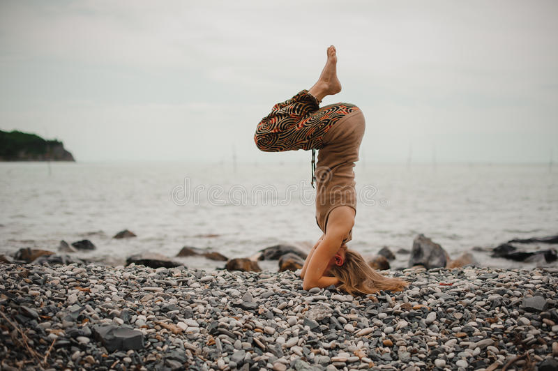 Woman standing on her head doing yoga royalty free stock photography