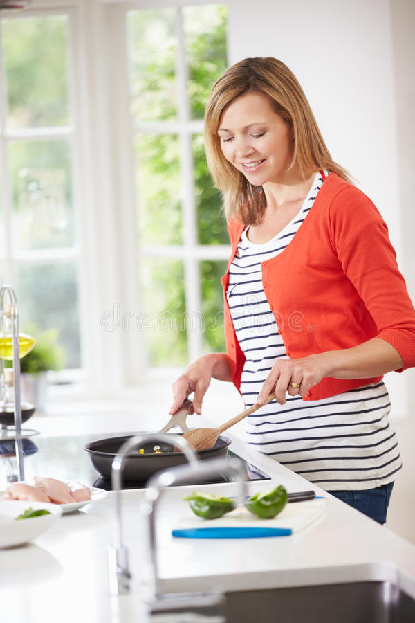Woman Standing At Hob Preparing Meal In Kitchen royalty free stock image