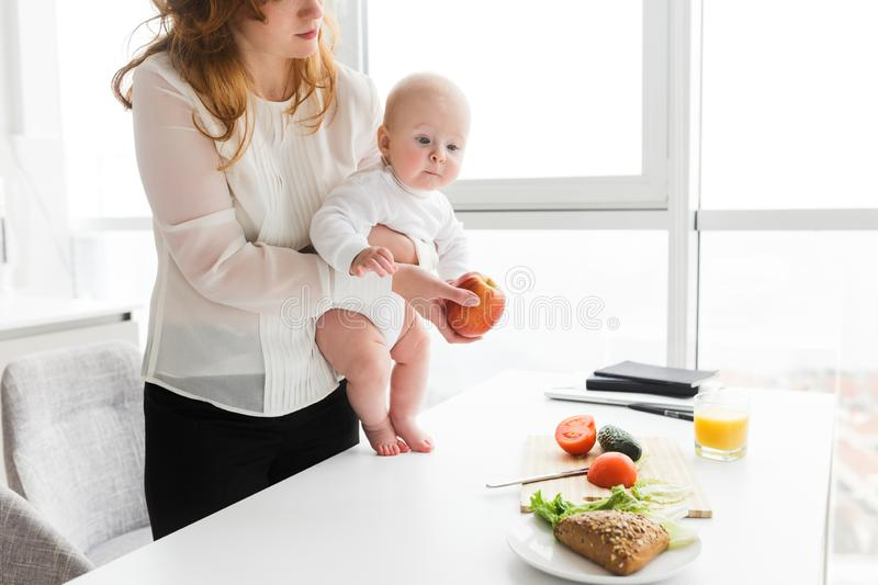 Woman standing and holding her cute little baby while cooking on kitchen royalty free stock image