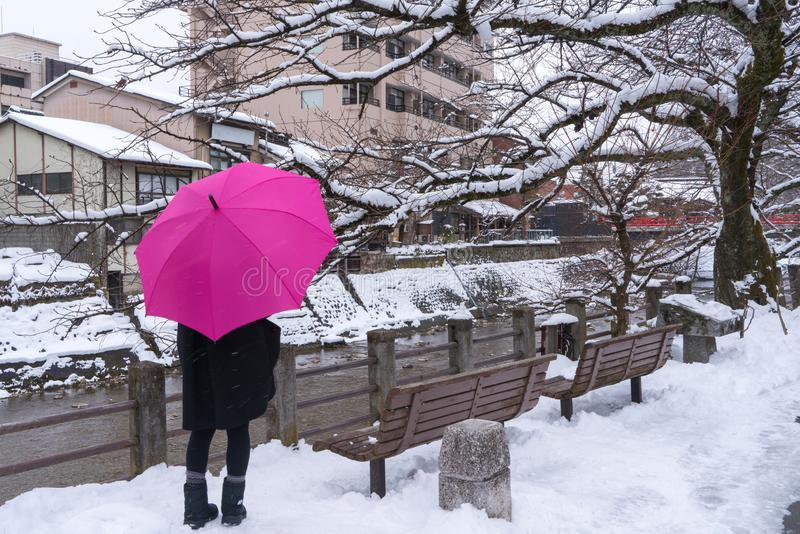 Woman standing and holding pink umbrella in the winter and snow is falling at Gifu Japan. Woman, standing and holding pink umbrella in the winter and snow is stock photo